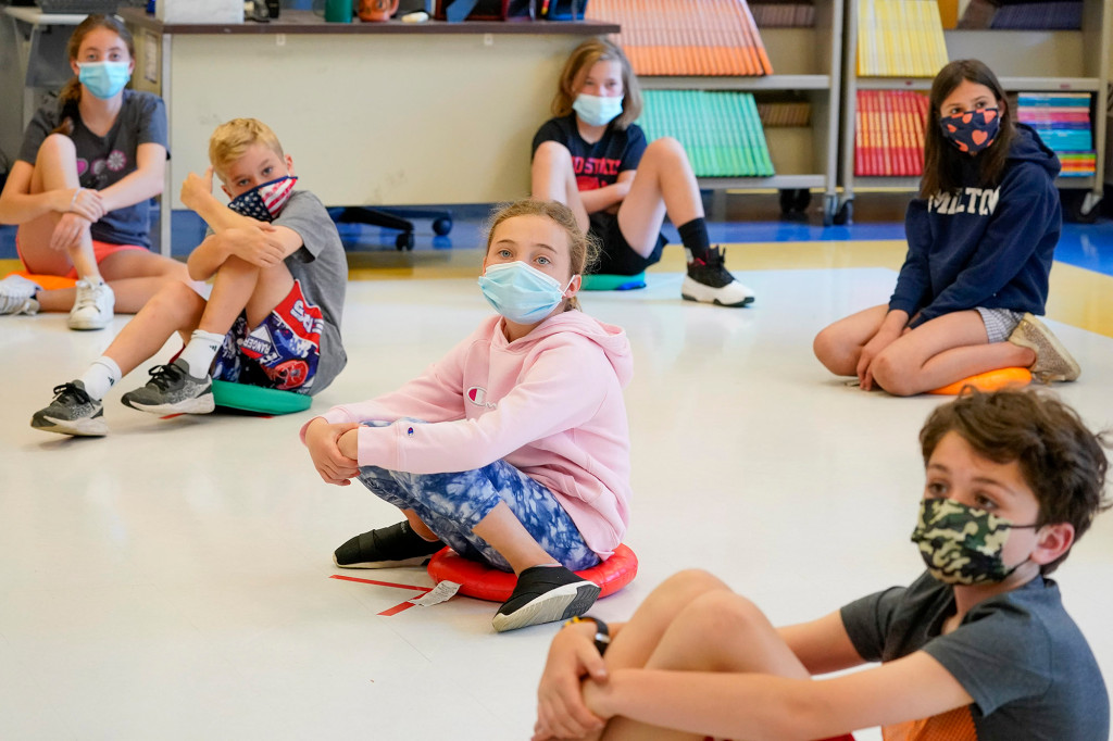 fifth graders wearing face masks are seated at proper social distancing during a music class at the Milton Elementary School in Rye, N.Y